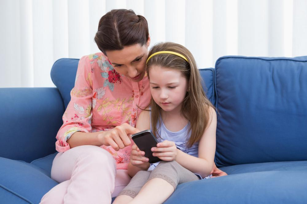 mother-and-daughter-using-smartphone-on-couch