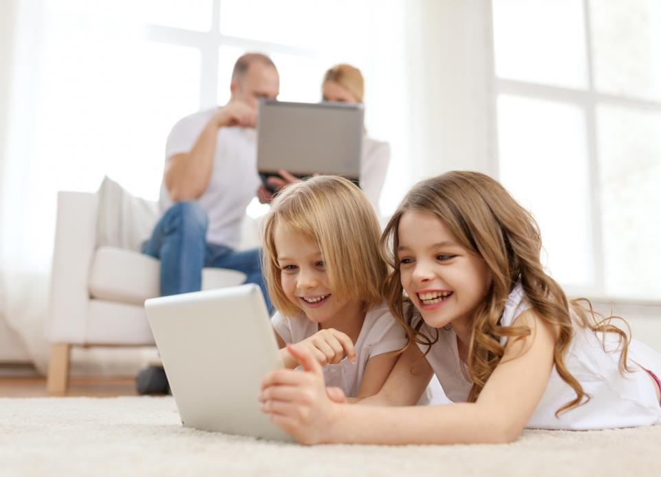smiling-sister-with-tablet-pc-and-parents-on-back