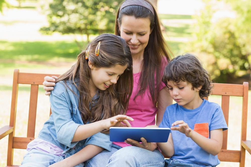 woman-with-kids-using-digital-tablet-in-park